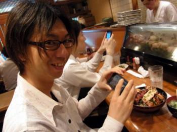 焼き鳥丼の写真を撮る右近さんの写真